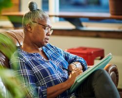 An older woman sits on a couch and writes in a notebook