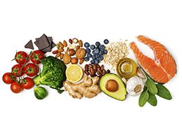 An assortment of heart healthy foods, including tomatoes, chocolate, broccoli, Brussels sprouts, nuts, lemon, ginger, blueberries, beans, ginger, avocado, oatmeal, olive oil, garlic, spinach and fish.