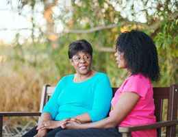 Two Black women sit on a bench.