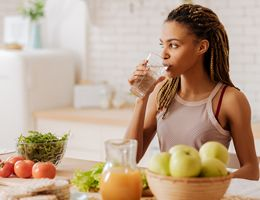 A woman drinks a glass of water at her kitchen counter