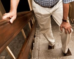 A man walking up stairs with one hand on the rail and the other on his knee.