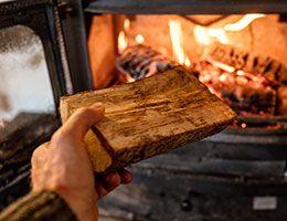 A hand holding a log reaches toward a fireplace.