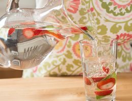 Jar and glass of strawberry agua fresca.