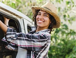 A woman in a straw hat leans out of a van.