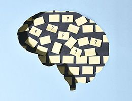Illustration of a brain with blank notes and notes with questions marks posted inside.