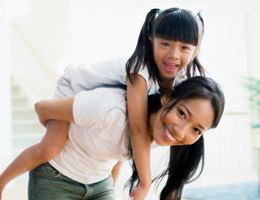 A mom giving her daughter a piggyback ride.