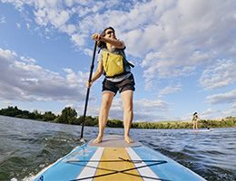 A middle-aged woman on a paddleboard in a lake.