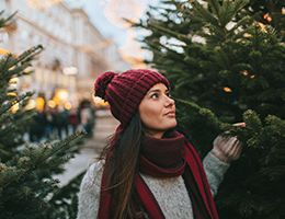 A young woman shopping for a Christmas tree alone.