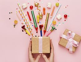 A open gift box with confetti, candy, straws and party horns spilling out.