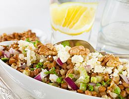 Lentil salad topped with fetta cheese in a white dish