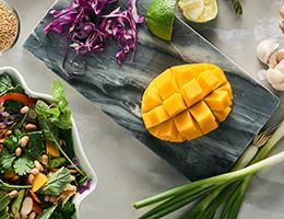 A mango on a cutting board with salad ingredients.
