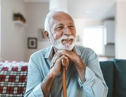 An older man sitting on a couch with his hands on his cane and his head leaning on his hands.