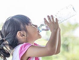 A little girl drinking water.