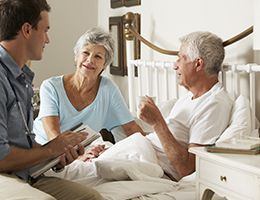 A healthcare worker visits a man and woman at home in bed.