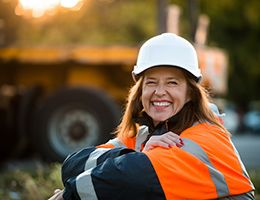 A smiling woman in a hard hat and orange jacket.