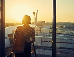 A woman standing in an airport and looking out a window at an airplane.