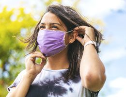 A woman puts on a cloth face mask.