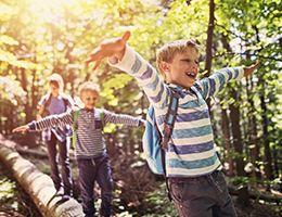 3 kids walking on a log while hiking.