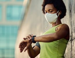 A masked woman wearing a tank top looks at her watch.