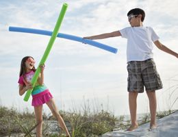 Two kids fencing with pool noodles.