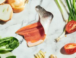 Fillet of fish surrounded by ingredients in recipe.