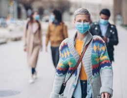 A woman in a face mask and sweater walks down a street.