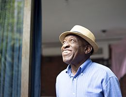 A smiling black man in a hat.