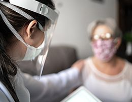 A healthcare worker in a mask and face shield touches the shoulder of a masked patient.