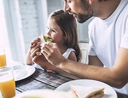 A father helps a child eat sandwich with lettuce.