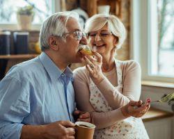 Older woman feeding avocado toast to spouse.