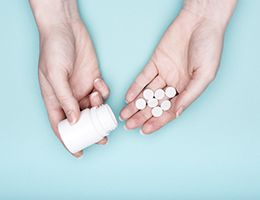 A pair of hands holding pills and a pill bottle.