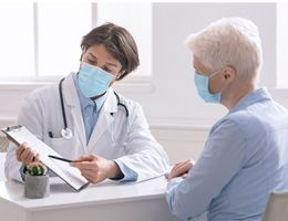 A masked healthcare worker and patient look at a clipboard together.