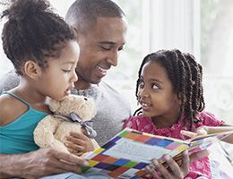 A father holds his two young daughters on his lap, reading to them from a brightly colored book. One girl points at a page, the other cuddles a teddy bear.