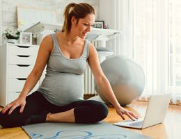 A pregnant woman sits on the floor and looks at a laptop.