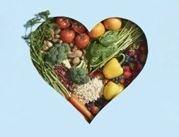 A variety of fruits and vegetables within a heart-shaped frame.