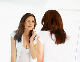A woman looks in a mirror and touches her face.