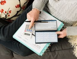A view of someone's lap from above with a checkbook, calculator and notebook.