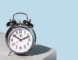 A silver alarm clock sits on a gray table in front of a blue wall