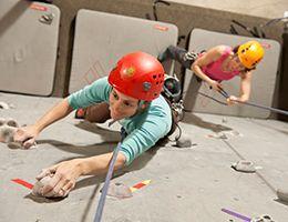 Two women using a climbing wall.
