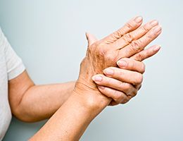 A woman with arthritic hands is gripping one hand with the other.