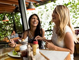 Two young Caucasian women laughing and eating in a restaurant.