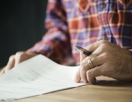 A person holding a pen reviews important documents.