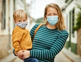 A woman and a toddler wearing masks outside.