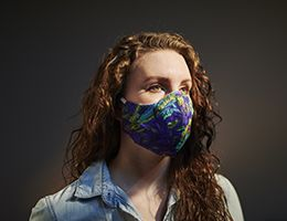 A woman wearing a colorful face mask.