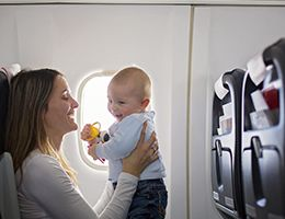 A mom holding a baby while seated on an airplane.