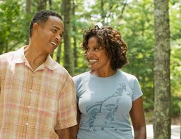 A Black man and Black woman stroll down a path in the woods, smiling