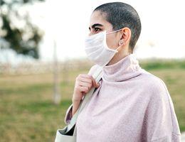 A woman in a face masks walks down a sidewalk.