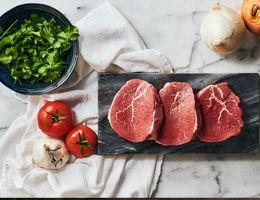 Lean beef on a black marble cutting board.