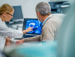 A female doctor is pointing to a brain scan while an older man looks at the scan.