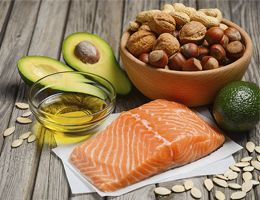 Salmon, avocados, oil, nuts and seeds on a wooden table.